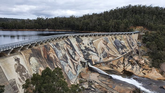 Wellington Dam with a mural painted on one side and water on the other side.