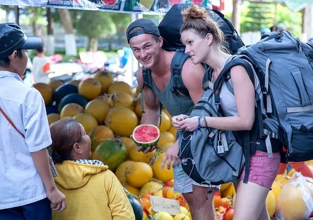 a couple wearing backpacks buying fruit at a local market showing what is backpacking all about