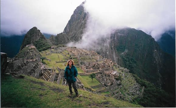 female hiker standing at the top of a mountain overlooking ancient ruins of Machu Picchu