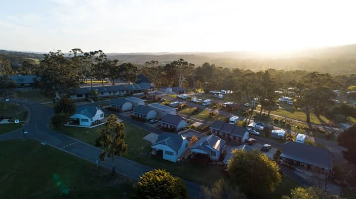 Aerial view of motorhome site with cabins and foreground and campground in background