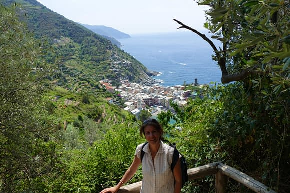 a female hiker standing at a viewpoint overlooking coastal village on the Cinque Terre hiking trails
