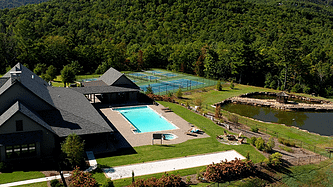 aerial view of a clubhouse, pool in the centre and tennis courts in the background