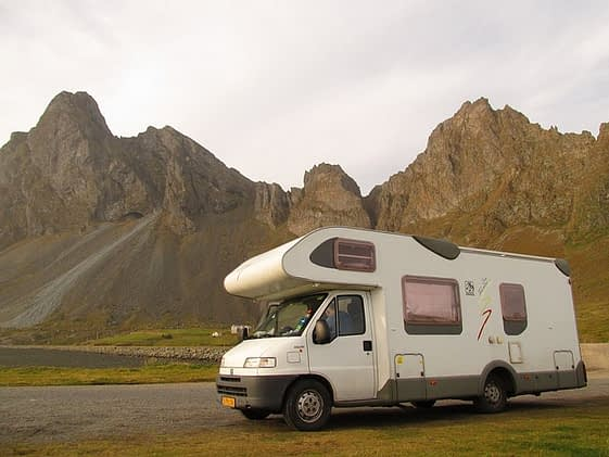 White motorhome parked by road with rocky peaks in the background