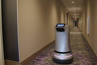 new travel trend for hotels with a cylinder shaped robot moving down hotel hallway with cold drinks inside