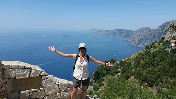 female hiker standing at a view point overlooking Amalfi coastline and sea