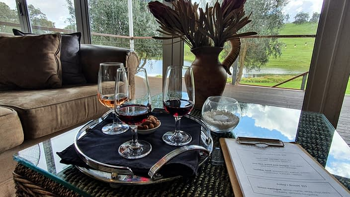 3 glasses of wine tastings on a silver platter, overlooking green pastures