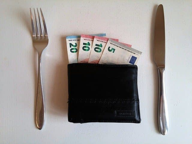 wallet with euros sticking out placed on table between fork and knife for budget travel