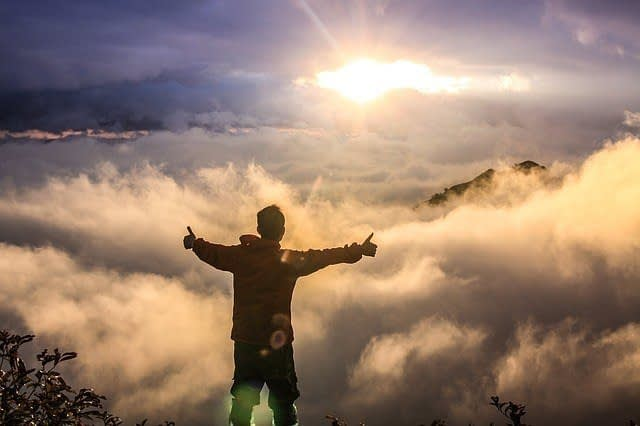 watching the sun while standing on mountain peak