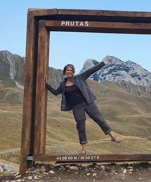 female standing in large wooden frame with mountains in background
