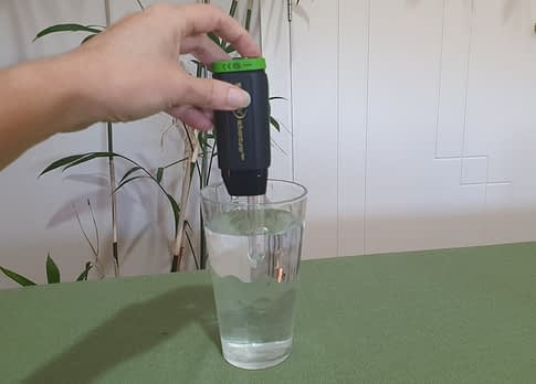 A hand holding a black coloured steripen with the clear tube immersed in a glass of water