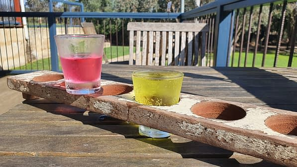 Two glasses with a pink and yellow drink, set inside a wooden tasting paddle