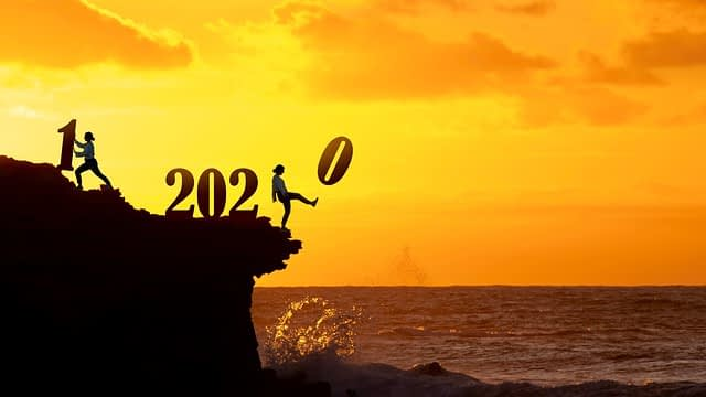person kicking 2020 off a cliff and pushing 2021 up a hill