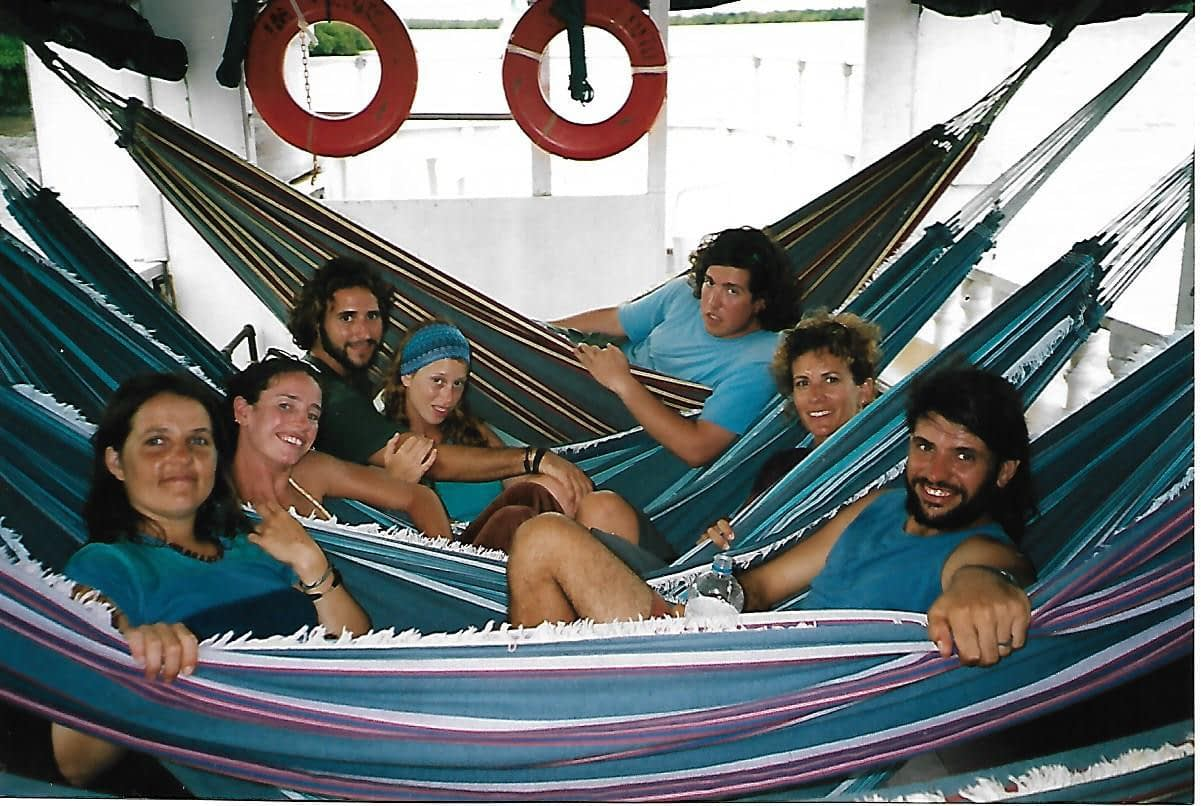 seven travellers laying in hammocks side by side