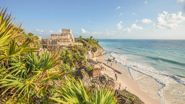 tulum ruins on top of a hilltop overlooking turquoise coloured beach below
