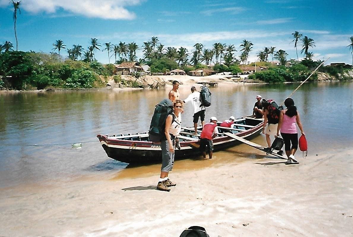 a group standing infront of small wooden to cross the narrow river