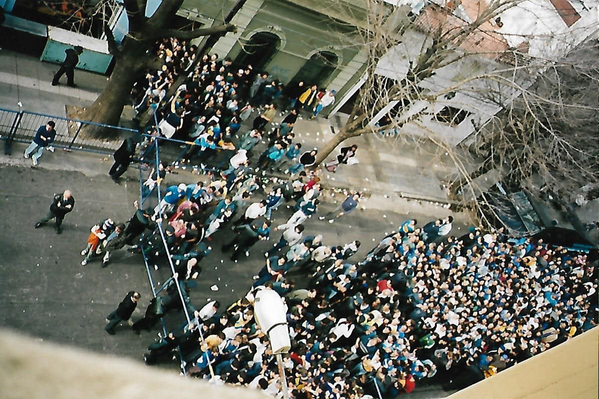 crowds of people lining up in a surburban street waiting to see football matches in Buenos Aires
