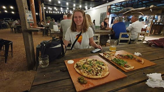 female sitting at bar with a pizza in front