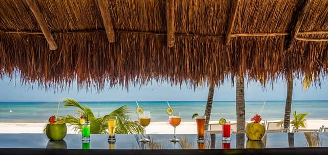 cozumel bar with different colour cocktails lined up on a wooden bar overlooking the beach