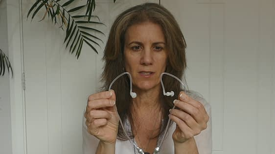 female holding air tube headphones to show the pre shaped tubing to fit over ears