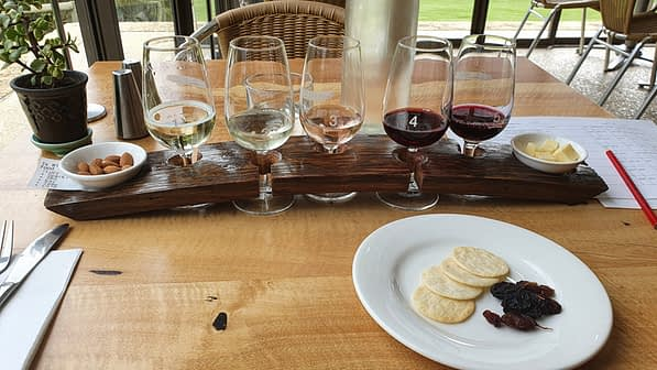 5 wine tasting glasses set in a wooden arched paddle, accompanied with nibbles