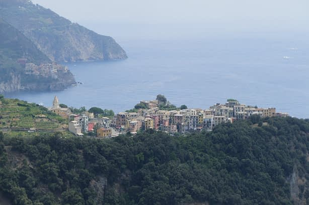 a small colourful village sitting ontop of a cliff with another clifftop town in the distance facing the sea.