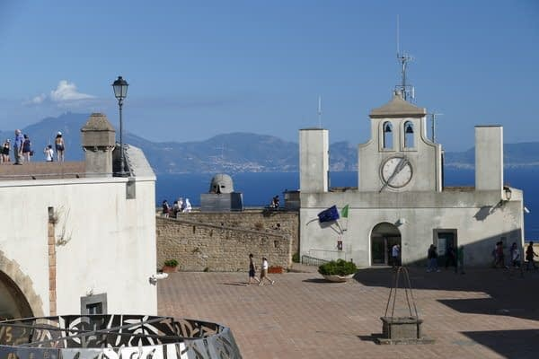 white coloured buildings and clock tower overlooking the sea