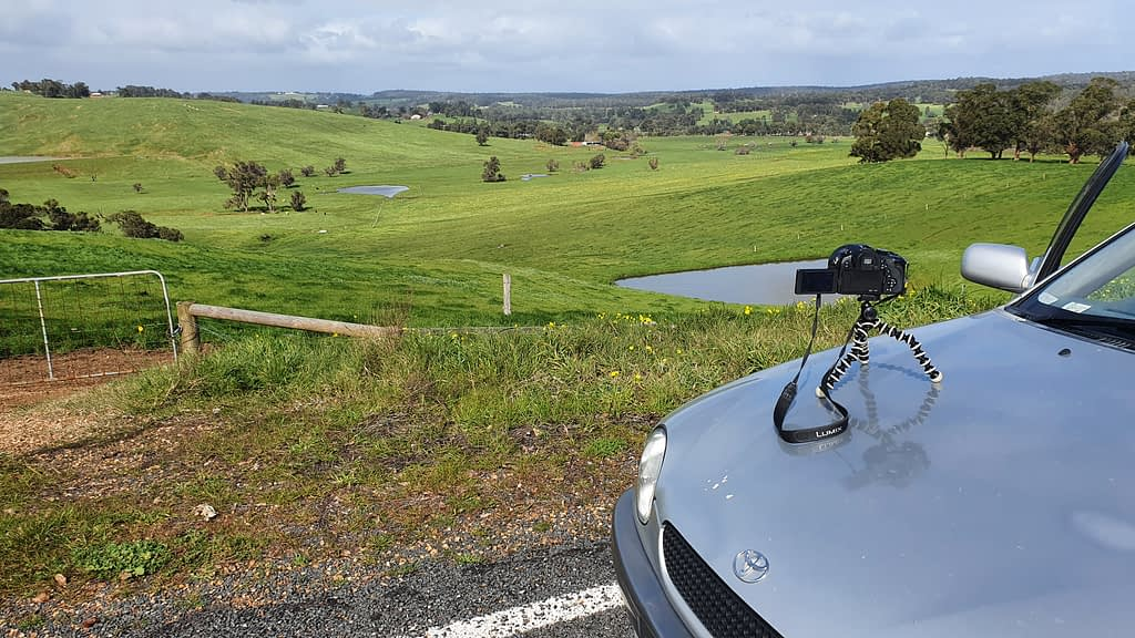 A camera sitting on the bonnet of a silver car overlooking Ferguson Valley
