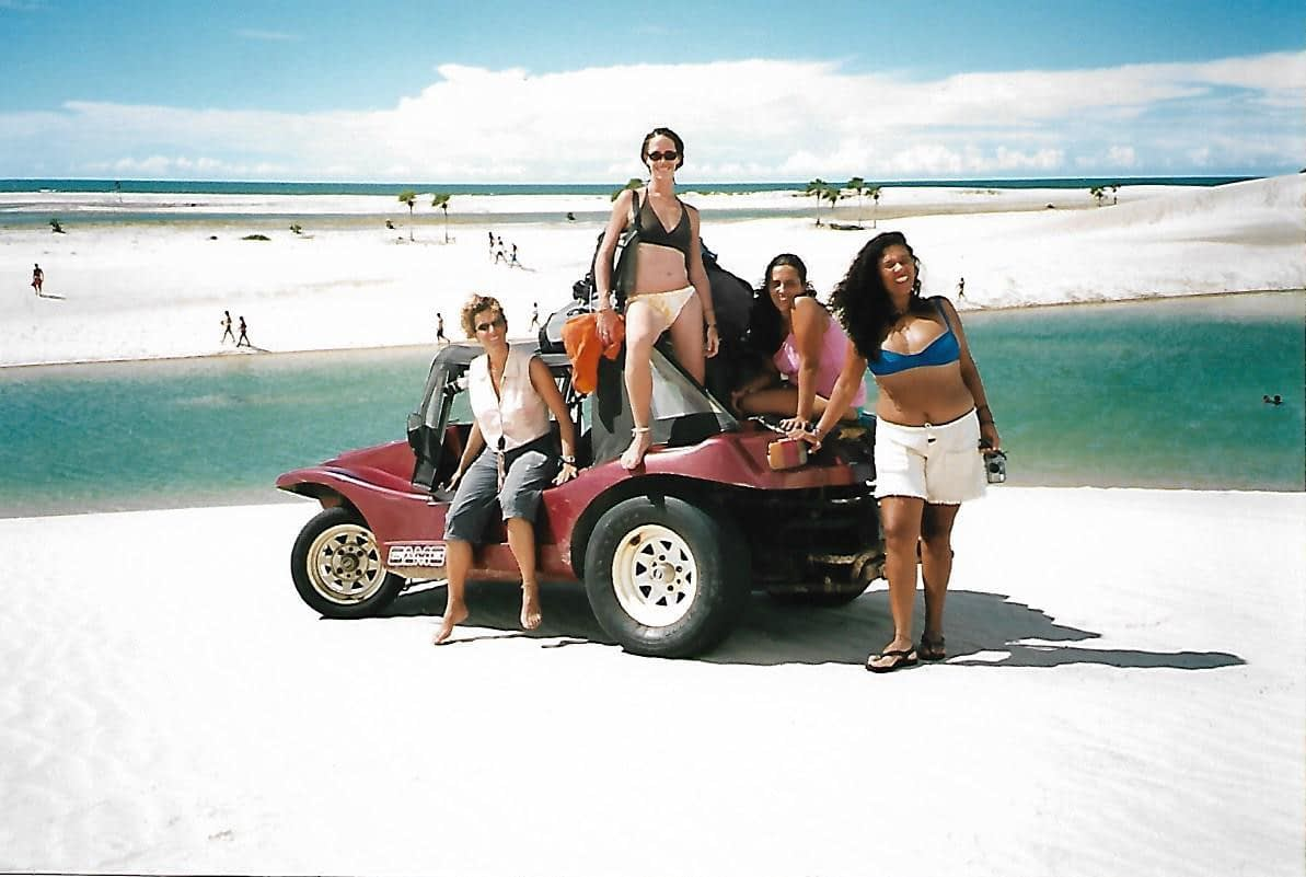 4 girls posing around a red beach buggy in white sand dunes