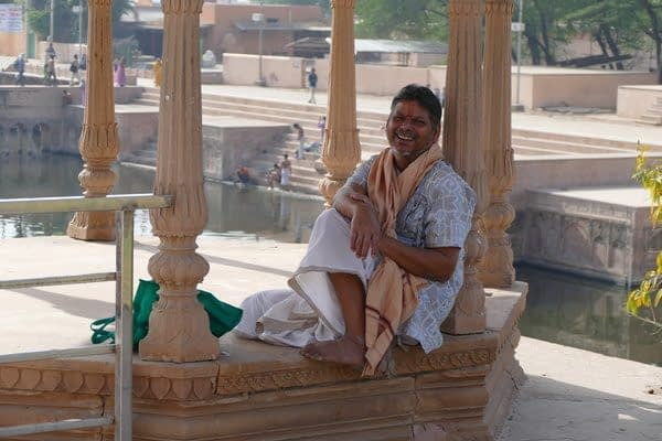 an indian guy relaxing and sitting in an outdoor temple