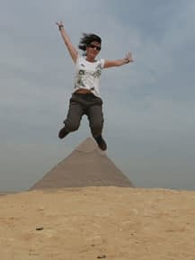 a female jumping high in front of giza pyramid while travelling in egypt