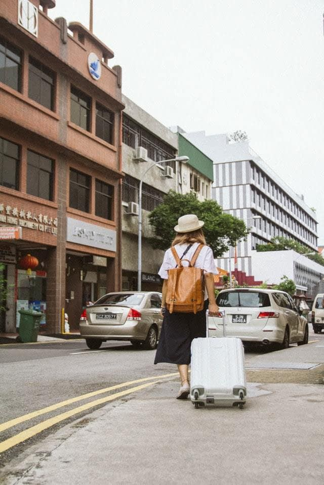 upmarket backpacking - a female walking along a street strolling her suitcase