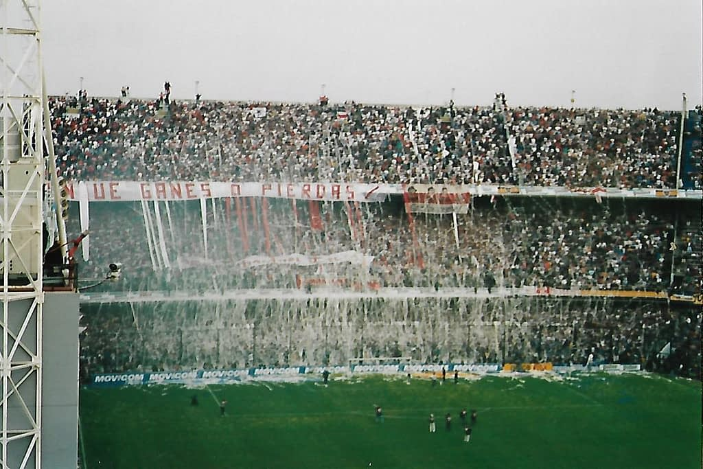 View of soccer stadium filled with fans and red/white ticket tape sprawling onto the ground