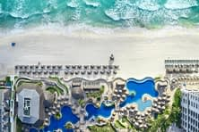 aerial view overlooking three pools and gardens and white sandy beach with turquoise water