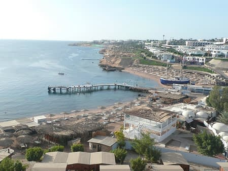 a coastal view of Sharm El Sheikh with many resorts and chairs on the beach