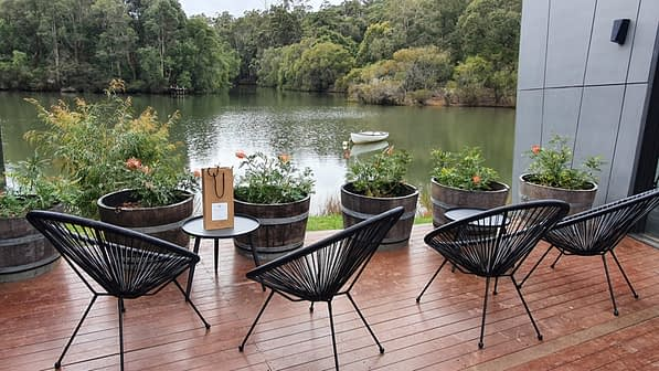 Four metal chairs set on wooden decking overlooking a large lake housing a white row boat
