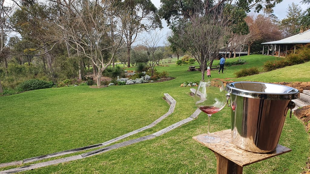 grassed area with trees in background and wine glass with silver bucket in foreground