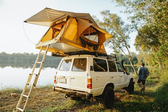 White 4WD parked by lake with a tent erect on its roof accessible by ladder