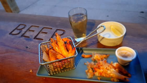 cooked prawns sitting a wired basket with glass of beer in background - things to do in exmouth