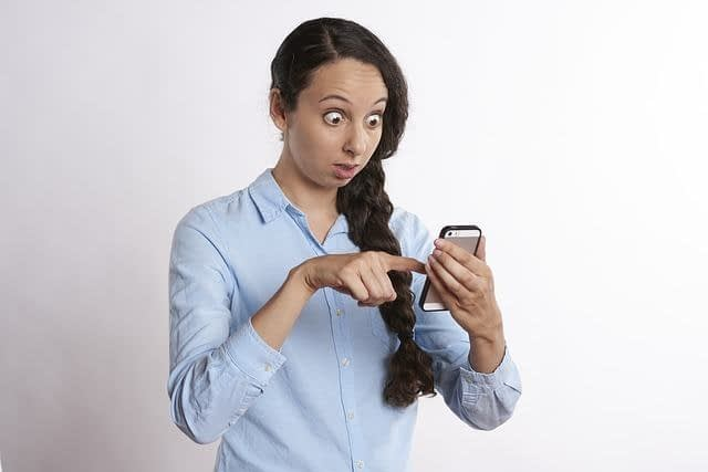 a lady scrolling on her phone with a shocked look on her face reading the high airline change fees
