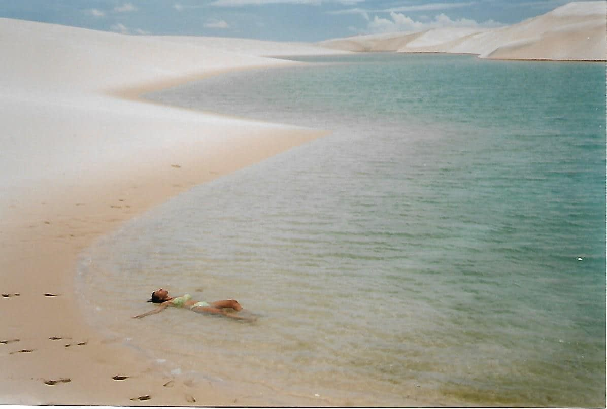 a female laying in a light blue lake surrounded by pure white sand dunes