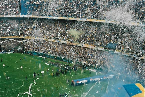 view of soccer stadium filled with fans streamers and smoke waiting for the players to appear