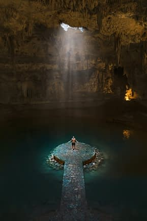 male standing at bottom of cave with light beaming down on him from a hole above