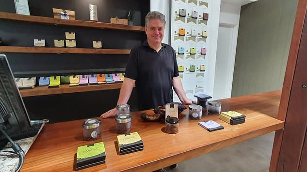 male standing behind counter displaying 5 different chocolates for tastings