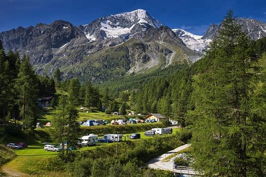 Two tiers of motorhome sites with swiss alps in the background