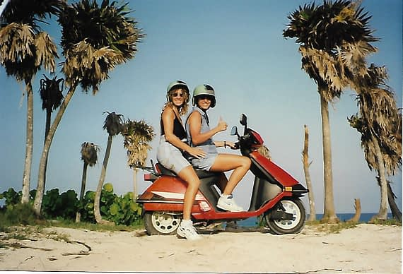 two females on a red scooter parked beside a cozumel beach