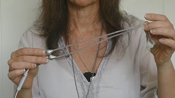 female hold air tube headphones to show the clear silicon tubing