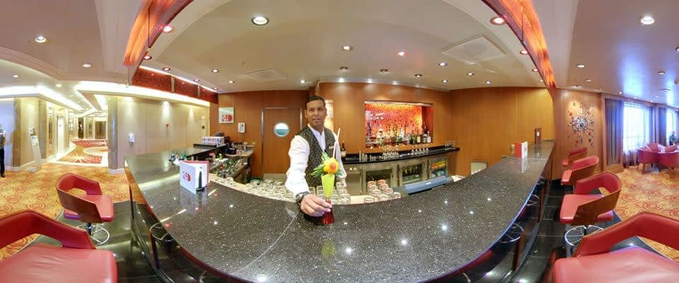 a ship bar with a waiter holding out a colourful cocktail drink