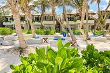 beach bean bags amongst palm trees with the 2 storey cabanas in the background